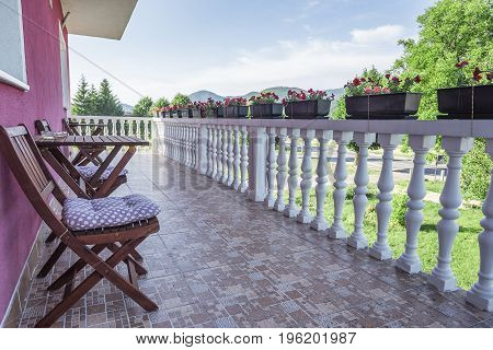 Balcony with a beautiful terrace with a table and chairs for rest.