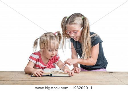 Senior sister pointer shows junior at something interesting in a book lying on a table, isolated on a white background