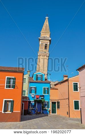 Burano, Italy - May 08, 2013. Overview of colorful buildings and leaning bell tower in a blue sunny day at Burano, a gracious little town full of canals, near Venice. Veneto region, northern Italy