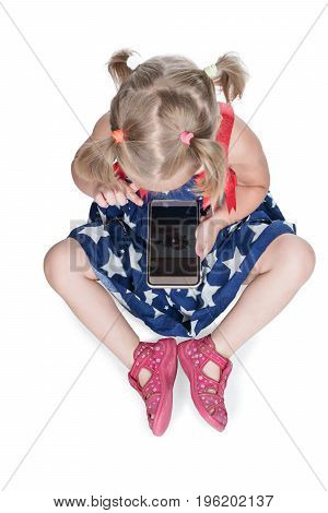 Little girl sitting on the floor using a smartphone, top view, isolated on a white background