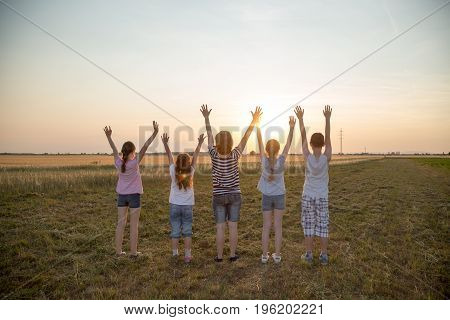 Five people standing in the field with raised hands above their heads, watching sunset