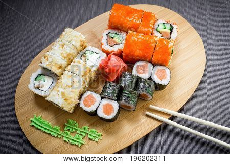 Japanese food - set of sushi rolls, sauce, wasabi and chopsticks on gray background. Top view. Flat lay