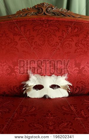A white feather owl mask on the seat of an antique couch with a red damask Victorian pattern upholstery.