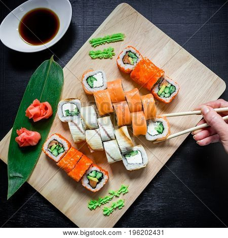 Sushi rolls and sauce and hand with chopsticks on a black background. Top view. Flat lay