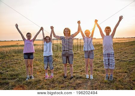 Four young children and one adult female holding hands in the air, standing at the field, facing camera. They are wearing casual summer clothes. Taken at summer sunset.