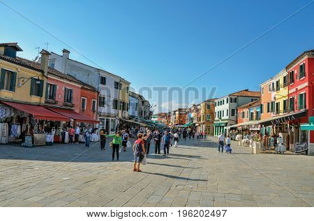 Burano, Italy - May 08, 2013. View of colorful houses in a square with people on a sunny day in Burano, a gracious little town full of canals, near Venice. Located in the Veneto region, northern Italy