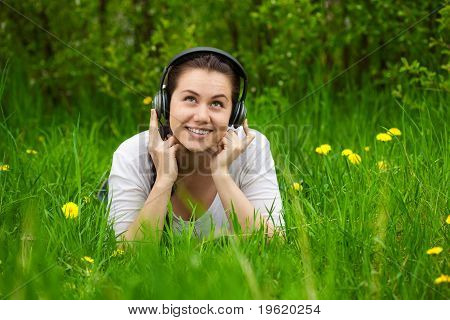 Girl With Headphones Lying In The Grass