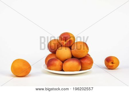 Fresh ripe apricots on a white saucer on a white background