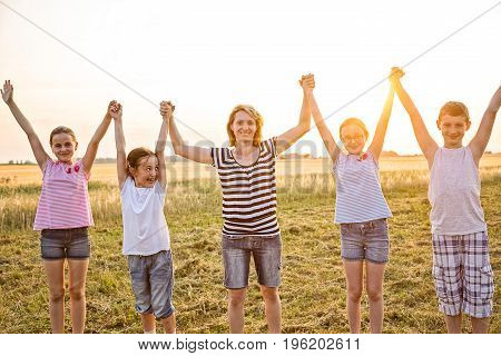 Four young children and one adult female holding hands in the air at summer sunset field