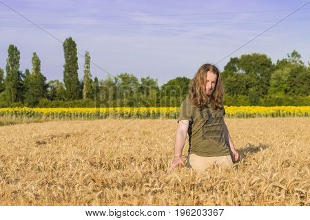 Young caucasian - nordic man with blond and long hairs among grain field