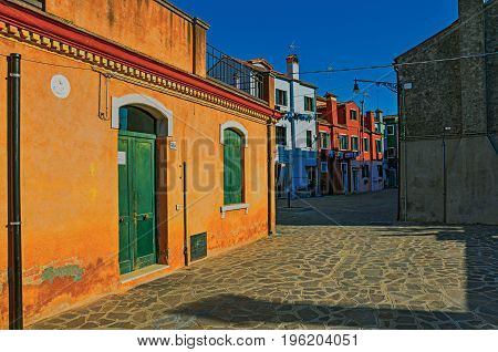 Overview of colorful terraced houses in an alley, in the sunset at the city center of Venice, the historic and amazing marine city. Located in the Veneto region, northern Italy. Retouched photo