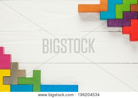 The concept of creative logical thinking. Frame with different colorful shapes wooden blocks on white background flat lay copy space. Geometric shapes top view. Abstract Background.