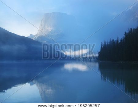 Morning mountain fog and reflection over the lake