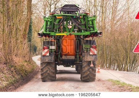 Tractor with Agricultural machine for spraying fertilizers or insecticides on a field.