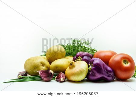 Assortment of fresh raw vegetables isolated on white background. Selection includes potato tomato green onion pepper garlic and dill