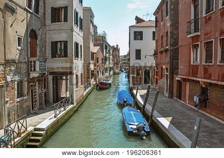 Venice, Italy - May 09, 2013. Overview of the canal with boats and buildings on the bank, at the city center of Venice, the historic and amazing marine city. Veneto region, northern Italy