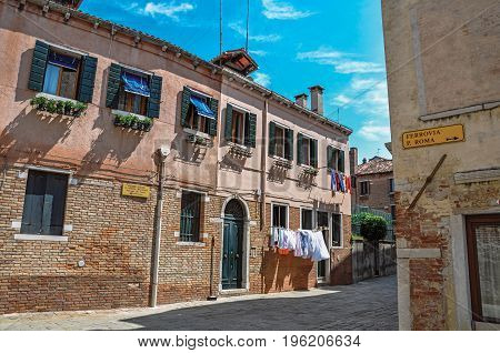 Overview of ancient houses and clothes hanging in an alley on sunny day. At the city center of Venice, the historic and amazing marine city. Located in Veneto region, northern Italy