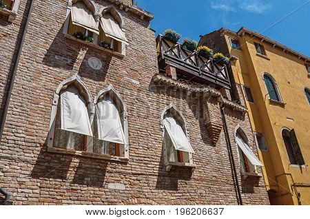 Overview of windows in old brick building with fabric blinds and blue sunny sky. At the city center of Venice, the historic and amazing marine city. Located in Veneto region, northern Italy