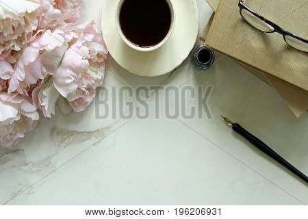 Pink peony bouquet, book stack, coffee, pen and ink, and eyeglasses against white marble background. Copy space.