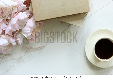 Pink peony bouquet, book stack and coffee against white marble background. Copy space.