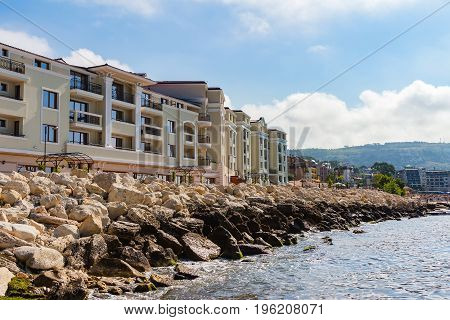 Apartment buildings on seashore with stones in bulgarian city balchik at black sea coast.