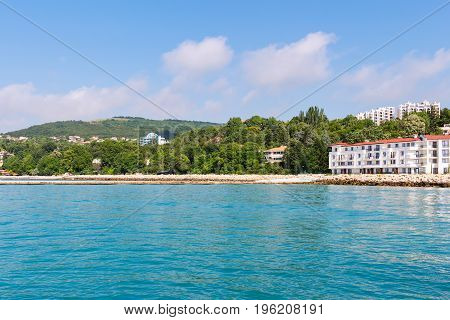 Seascape with azure water and green hills on shoreview on black sea coast with buildings and houses in balchik city Bulgaria.