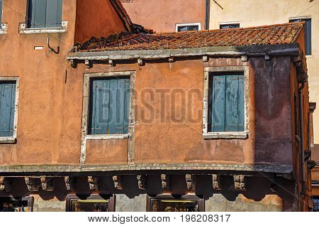 Close-up of windows in medieval house with green blinds closed. At the city center of Venice, the historic and amazing marine city. Located in Veneto region, northern Italy