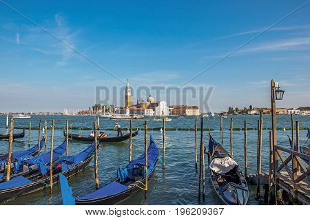 Venice, Italy - May 08, 2013. Panoramic view of Venice lagoon with pier and gondola in front and buildings behind. At the city of Venice, the historic and amazing marine city. Veneto region