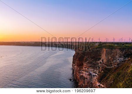 Sunset on cape Kaliakra with windmills farm huge cliffs on black sea coast in Bulgaria.