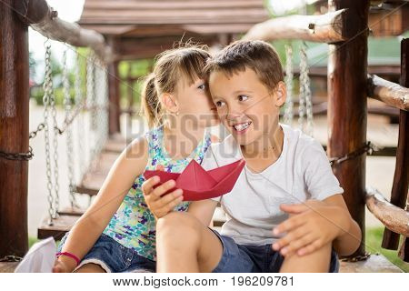 Happy two caucasian siblings sittign in a wooden house outdoors on summer day holding a paper boats in their hands girl whispering a secret to a boy´s ear