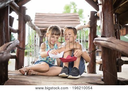 Two young caucasian children sitting next to each other with bent knees in a wooden house outdoors on sunny summer day playing with paper boats