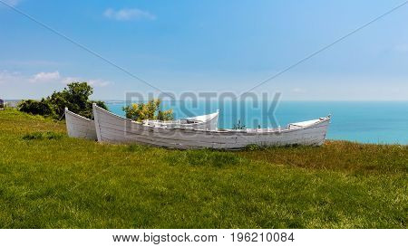 Two white broken old boats on the grass view from altitude to the sea black sea coast in Bulgaria.
