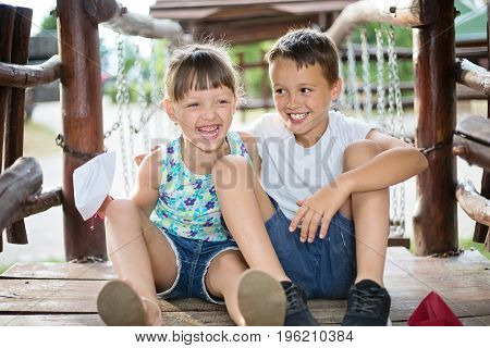 Two young caucasian children sitting next to each other with bent knees in a wooden house outdoors on sunny summer day bursting in laugh