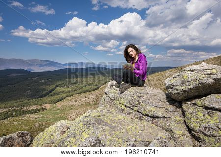 Woman Sitting On Top Of Mountain Typing In Tablet