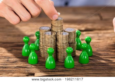 Close-up Of A Businessperson Placing Coins Over Stack With Green Figures On Wooden Desk