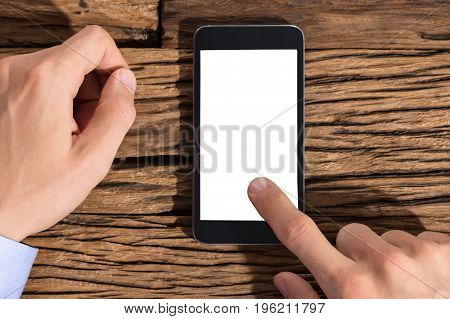 Close-up Of A Businessperson Using Smart Phone With Blank White Screen Against Wooden Background