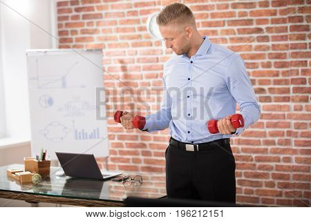 Attractive Businessman Exercising With Red Dumbbells In Office