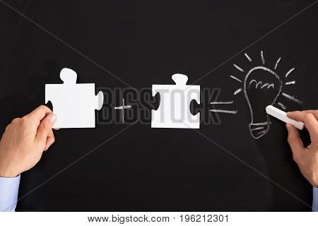 Person Drawing Idea Equation With White Puzzles On Black Blackboard