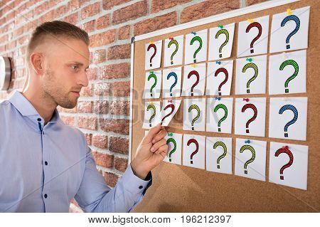 Close-up Of A Businessman Looking At Question Marks On Notes Attached Over Bulletin Board