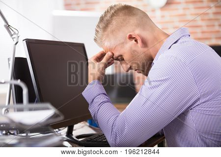 Businessman Suffering From Headache Sitting In Front Of Computer