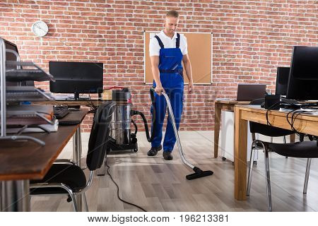 Happy Male Janitor Cleaning Floor With Vacuum Cleaner At Workplace