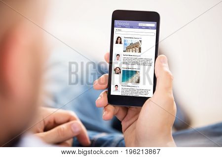 Close-up Of Young Man Surfing On Social Networking Site Using Cellphone