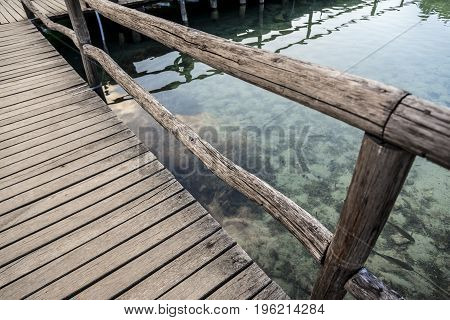 Part of a wooden pier on a crystal clear lake.