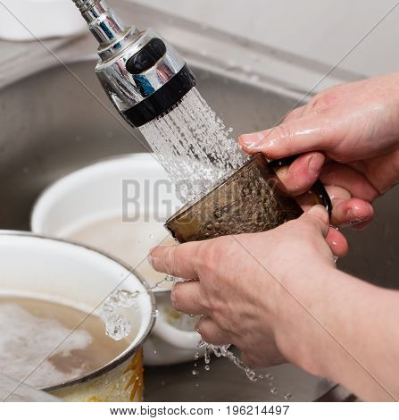 Woman washes spoons under a tap of water .