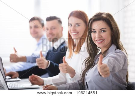 Smiling Woman With Her Colleagues Showing Thumb Up Sign In Office
