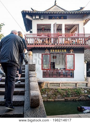 Suzhou, China - Nov 5, 2016: At the historic Zhouzhuang Water Town. People walking across a stone bridge towards a restaurant building designed with traditional architectural styling.