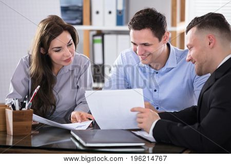 Couple Talking With Advisor During Meeting In Office