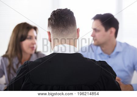 Rear View Of A Male Judge Sitting In Front Of Couple Quarreling