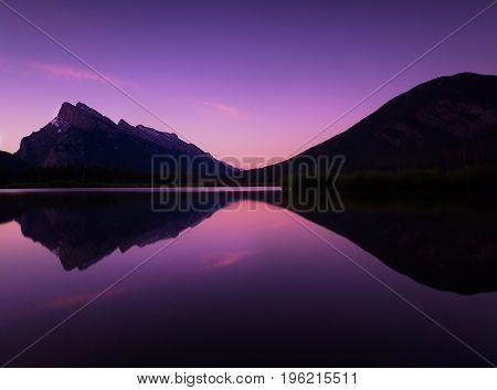 Purple Rocky Mountains Sunrise Reflecting on Still Lake