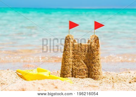 Red Flags On Sandcastle Made Near The Coast At Beach